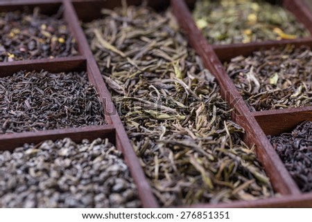 Assortment of dry tea leaves in wooden box - stock photo