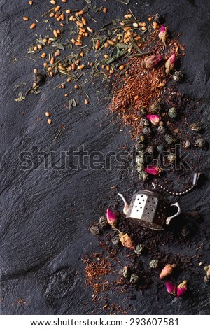 Assortment of dry tea with tea strainer as small teapot. Green tea, black tea, green tea with rice, rooibos, dry rose buds. Black textured slate background. Top view. With copy space on left - stock photo