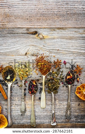 assortment of dry teas in silver spoons on wooden background - stock photo