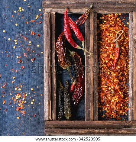 Assortment of dryed whole and flakes red hot chili peppers in wooden box over dark blue canvas as background. Top view. Square image - stock photo