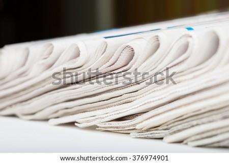 Assortment of folded newspapers closeup. Shallow DOF. - stock photo