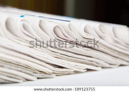 Assortment of folded newspapers closeup. Shallow DOF. Breaking news, journalism, power of the media, newspaper and magazine ads and subscription concept. Great as a web page banner or header and more. - stock photo