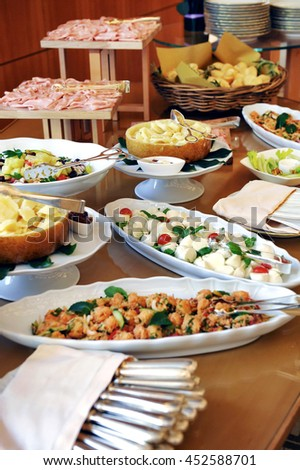 Assortment of food on a cold buffet at a hotel or catered event with sliced cold meats, salads and fish on display on individual plates