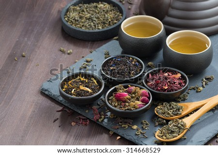 assortment of fragrant dried teas and green tea on wooden table, horizontal, close-up - stock photo