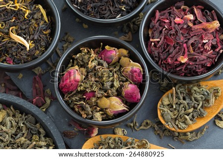assortment of fragrant dry tea in ceramic bowls, close-up, top view, horizontal - stock photo