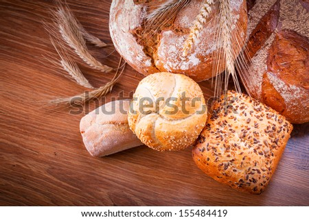 Assortment of fresh bread on wooden table - stock photo
