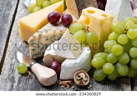 assortment of fresh cheeses and grapes on a wooden background, top view, close-up