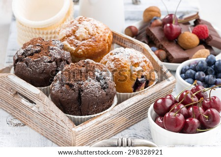 assortment of fresh delicious muffins and fresh berries for breakfast, closeup, horizontal - stock photo