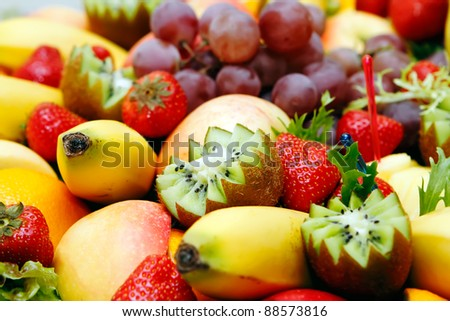 Assortment of fresh fruit, focused to banana on the left and kiwi in the middle - stock photo