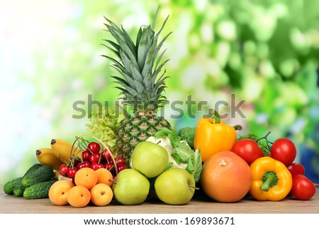 Assortment of fresh fruits and vegetables on natural background - stock photo