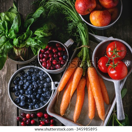 Assortment of fresh fruits, vegetables and berries. Bunch of carrots, spinach, tomatoes and red apples, blueberries and cranberries in vintage aluminum utensil over old wooden table. Top view - stock photo