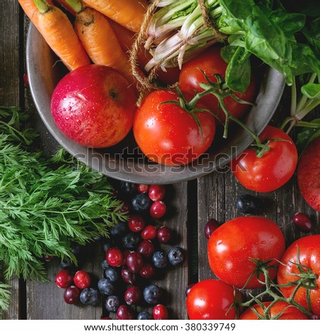 Assortment of fresh fruits, vegetables and berries. Bunch of carrots, spinach, tomatoes and red apples in vintage metal bowl, blueberries and cranberries over old wooden table. Top view. Square image  - stock photo
