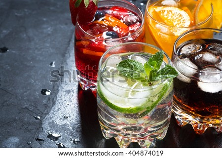 assortment of fresh iced fruit drinks on a black background, closeup - stock photo