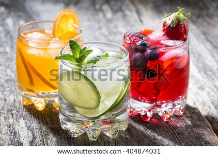 assortment of fresh iced fruit drinks on wooden background, horizontal