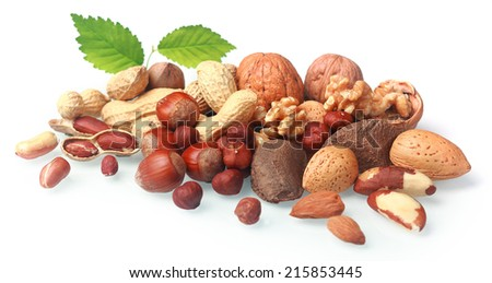 Assortment of fresh nuts both in their shells and shelled arranged in a pile on a white background with green leaves including almonds, hazelnuts, brazil nuts, peanuts and walnuts