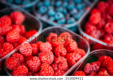 Assortment Of Fresh Organic Red Berries Raspberries And Blueberries At Produce Local Market In Baskets, Containers. - stock photo