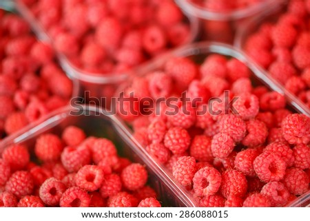 Assortment Of Fresh Organic Red Berries Raspberries At Produce Local Market In Baskets, Containers. - stock photo