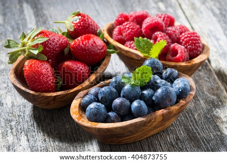 assortment of fresh seasonal berries in a wooden bowl, closeup - stock photo