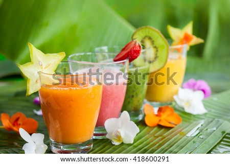 Assortment of fresh  tropical fruits smoothies on the green banana leaves - stock photo