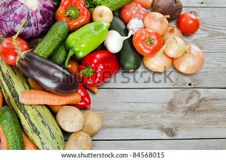 Assortment of fresh vegetables on wooden background - stock photo