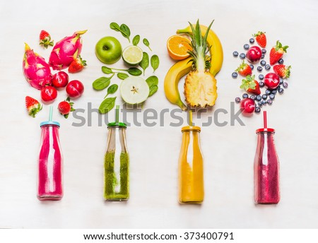 Assortment of fruit  and vegetables smoothies in glass bottles with straws on white wooden background. Fresh organic Smoothie ingredients. Superfoods and health or detox  diet food concept.