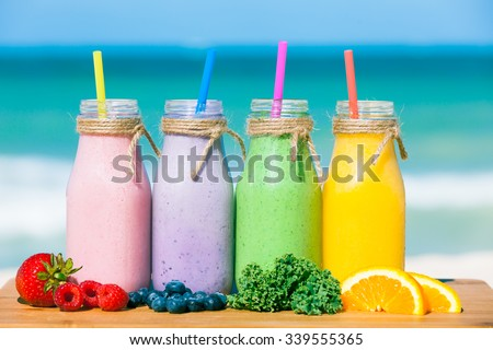 Assortment of fruit smoothies against a beach background - stock photo