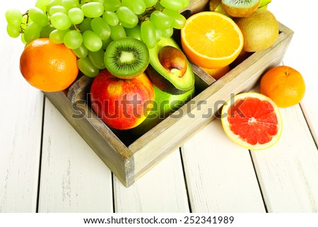 Assortment of fruits in box on wooden table - stock photo