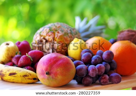 Assortment of fruits on wooden table on green background - stock photo