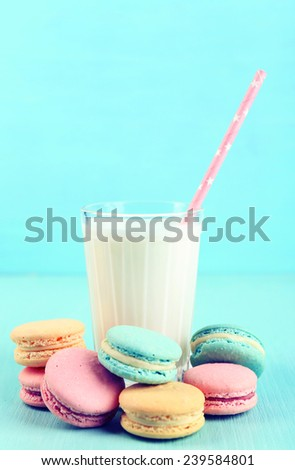 Assortment of gentle colorful macaroons and glass of milk on color background