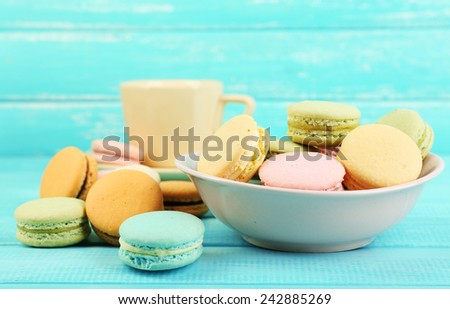 Assortment of gentle colorful macaroons in colorful bowl and mug with milk on color wooden background - stock photo
