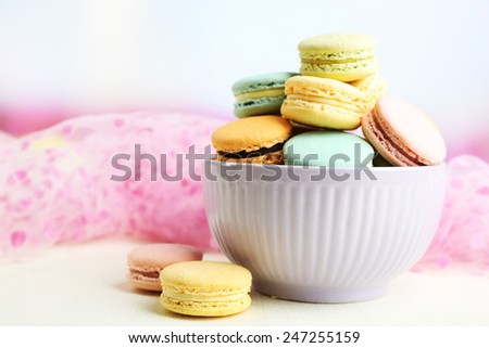 Assortment of gentle colorful macaroons in colorful bowl on color wooden table, on light background