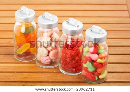 Assortment of glass jars with marshmallows, candies and red licorice on wooden background. Shallow depth of field - stock photo