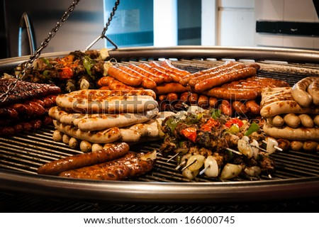 Assortment of grilled sausages and kebabs on big hanging grill at Christmas market in Paris. Shadowed angles. - stock photo