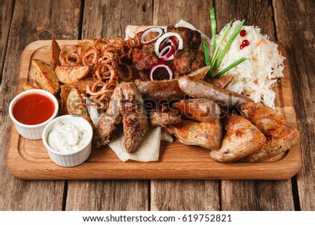 Assortment Of Grilled Sausages And Meat Served With Pita Bread Fried Potato Wedges Onion