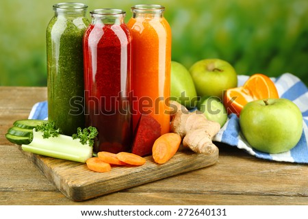 Assortment of healthy fresh juices in glass bottles on wooden table, on bright background - stock photo