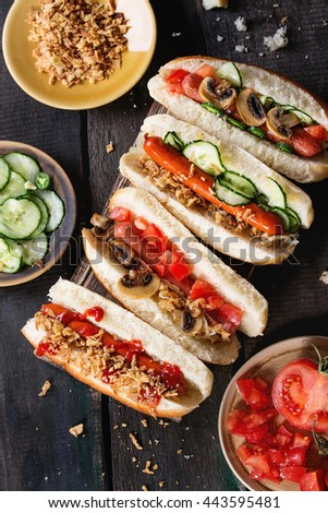 Assortment of homemade hot dogs with sausage, fried onion, tomatoes and cucumber, served with ingredients in different plates on wood chopping board over old wooden background. Rustic style. Top view - stock photo