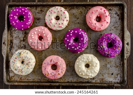 Assortment of homemade vanilla bean donuts with colorful icing sitting on metal baking pan - stock photo