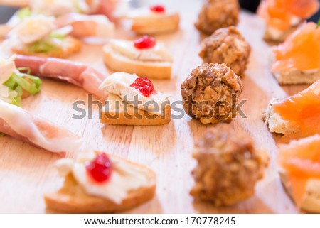 Assortment of Hors D'oeuvres on a wooden platter - stock photo