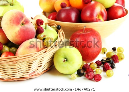 Assortment of juicy fruits in wicker basket and wooden bowl, isolated on white - stock photo