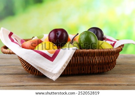 Assortment of juicy fruits in wicker basket on table, on bright background - stock photo