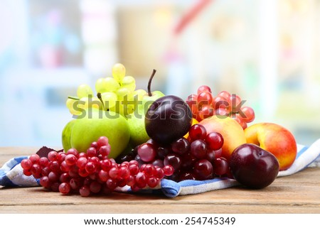 Assortment of juicy fruits on napkin, on table, on bright background - stock photo