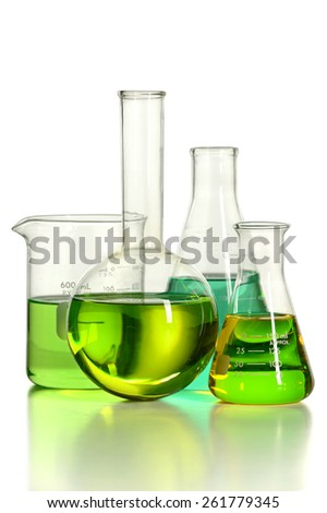 Assortment of laboratory glassware with green liquid isolated over white background -With clipping path on glass - stock photo
