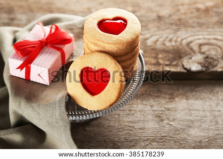 Assortment of love cookies with gift and cloth on wooden background, closeup - stock photo