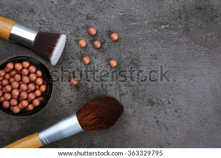 Assortment of make-up brushes and blusher, on grey background - stock photo