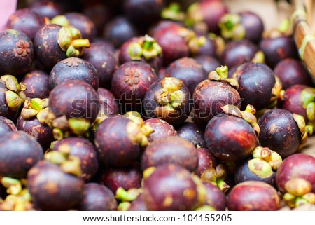 Assortment of mangosteen fruits at market stall - stock photo