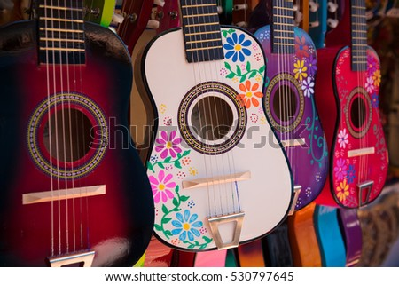 Assortment of Mexican made wooden acoustic guitars in a variety of colors