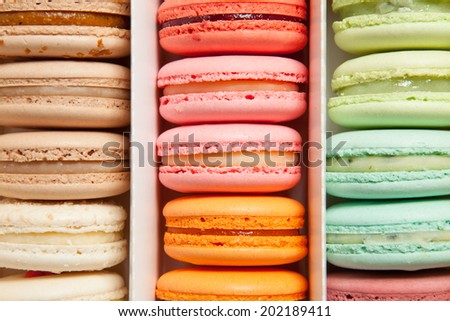 Assortment of multicolored macaroon different lie in the cardboard box with the top view - stock photo