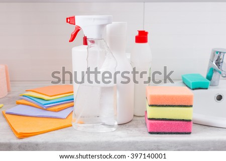 Assortment of new household cleaning products arranged alongside the hand basin in a bathroom with cloths, containers, dispensers and colorful sponges - stock photo