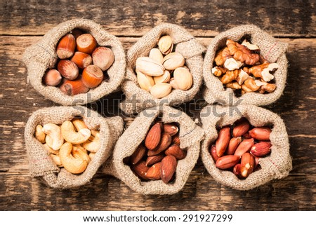 Assortment of nuts on wooden old table,healthy vegan food.