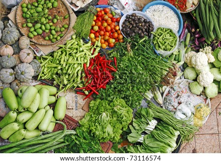 Assortment of organic farm produce spread out for display on a wet market vendor stall. - stock photo